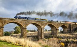 Old Fashioned Steam Train Crossing a Historic Bluestone Masonry Bridge, Malmsbury, Victoria, Australia, June 2019 stock image