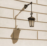 Old-fashioned street lamp with shadow. Old fashion street lamp with shadow on the building wall Stock Photo