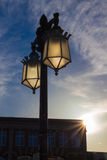 Old Fashioned Street Lamps. Silhouetted against a partly cloudy sky with a low sun in the background royalty free stock photos