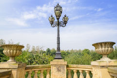 Old-fashioned streetlamp on stone balustrade against blue sky in Stock Photos