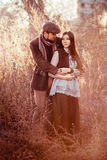 Old-fashioned stylish couple at sunset among tall grass and bushes lit by setting sun. Royalty Free Stock Photo