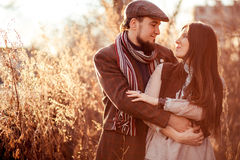 Old fashioned stylish young couple at sunset among tall grass illuminated by the setting sun. Stock Images