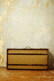Old-fashioned suitcase. Standing on the old wooden floor against a shabby wall royalty free stock photos