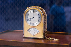 Old fashioned table clock. In shop with blue background royalty free stock photo