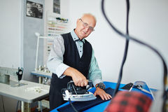 Old Fashioned Tailor Ironing in Atelier Stock Photography