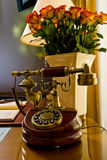 Old fashioned telephone. Old-fashioned telephone on a desk with a vase of roses and a lamp Stock Images