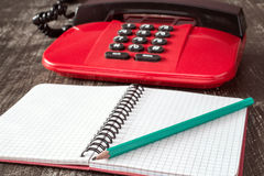 Old fashioned telephone and empty notebook Royalty Free Stock Photo