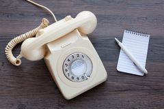 Classic telephone with notebook and pen. Old fashioned telephone together with a notebook and pen stock photography