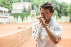 Old-fashioned tennis player with towel drinking water after training. On tennis court stock photo