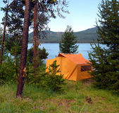 Old fashioned tent. A yellow orange old fashioned tent at Diamond Lake. Green Grass and trees surround the tent with the lake in the background Stock Images