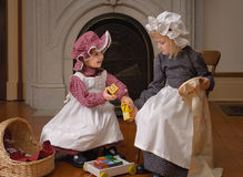 Old-fashioned Time. Sister doing needlework and assisting sibling with her block play, Victorian dress Royalty Free Stock Photo