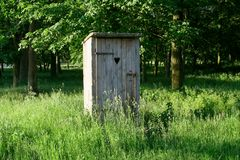 Old fashioned toilet building with wooden door standing outside among the grass with trees in the background. A scene presenting old fashioned toilet building royalty free stock images