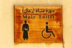 An old-fashioned Toilet sign hanging on a wall. Stock Image