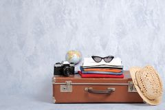 Free Old Fashioned Travel Suitcase With Summer Accessories: Glasses, Pack Of Clothing, Retro Photo Camera, Straw Beach Hat On Grey Back Stock Images - 142210274