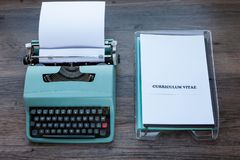 Document in a filing tray - Curriculum Vitae. Old fashioned typewriter with plastic filing tray and the words Curriculum Vitae stock image
