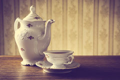 Old-fashioned vintage jug with tea with wallpaper background. Old-fashioned porcelain jug with a cup of tea with old-fashioned wallpaper background stock photos