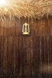 Old fashioned vintage kerosene oil lantern lamp with aged wooden wall. And weathered grass roof stock photography