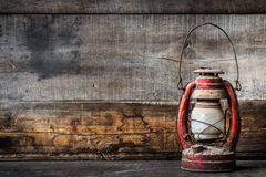 Old fashioned vintage kerosene oil lantern lamp burning with a soft glow light with aged wooden floor Royalty Free Stock Photo