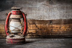 Old fashioned vintage kerosene oil lantern lamp burning with a soft glow light with aged wooden floor Royalty Free Stock Image