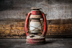 Old fashioned vintage kerosene oil lantern lamp burning with a soft glow light with aged wooden floor Stock Image
