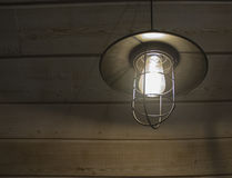 Old fashioned vintage lantern lamp burning with a soft glow light in an antique rustic country barn with aged wood wall Stock Image
