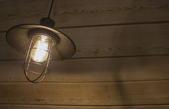 Old fashioned vintage lantern lamp burning with a soft glow light in an antique rustic country barn with aged wood wall Royalty Free Stock Image