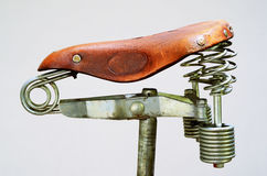 Old-fashioned vintage leather bike saddle. With metal spring Stock Photos