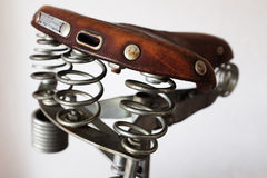 Old-fashioned vintage leather bike saddle. With metal spring Stock Photo