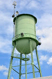 Old Fashioned Vintage Water Tower. Old fashioned vintage light green water tower against beautiful cloudy blue sky Stock Images