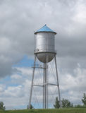 Old fashioned water tower on a hill. Old fashioned gray metal with a blue cone top small town water tower sitting on the top of a hill in the prairie. Clouds royalty free stock images
