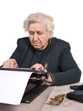 Old-fashioned way. Old lady working an old-fashioned way with typewriter royalty free stock photography