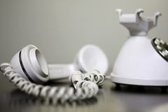 Old Fashioned White Telephone off the Hook. An old fashioned, vintage style white telephone has the receiver off the hook, and is sitting on a table, with room Stock Photos