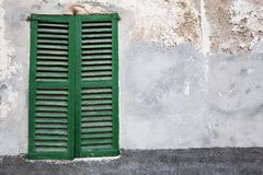 Old-fashioned window with green closed shutters Royalty Free Stock Images