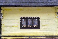 Old-fashioned window of wooden house in Vlkolinec. Old-fashioned window of wooden house on yellow wall in Vlkolinec Stock Image
