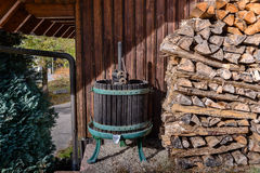 Old fashioned wine press next to pile of logs Royalty Free Stock Photos