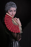 Old fashioned woman with fan. Half body portrait of young woman in old fashioned or vintage era clothes, black background Stock Image