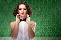 Old fashioned woman on vintage green background. Professional make up and hairstyle. Studio lighting stock images