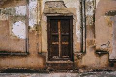 Old fashioned wooden door. In a cracked grungy wall Stock Photo