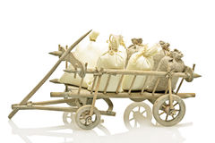 Old fashioned wooden handcart with bags of straw and potatoes Stock Image