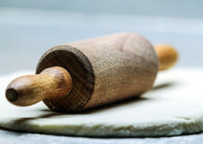 Old-fashioned wooden rolling pin on dough Royalty Free Stock Image