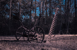 Old Fashioned Work Ethic. Vintage farm implement left behind to rust.  Old plows and farm equipment litter the landscape in some rural areas Stock Photography