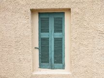 Old fashioned worn window with green wooden shutters, closed, on plastered wall background. Traditional house facade, old town of Plaka, Athens Greece stock photos