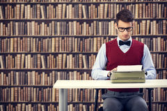 Old-fashioned writer. Young old-fashioned writer with typewriter in library Stock Photography