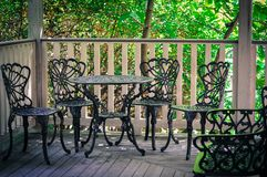 Wrought iron patio furniture. Old fashioned wrought iron patio furniture on wooden porch or balcony against green trees Royalty Free Stock Photo