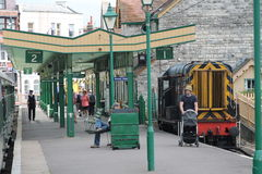 Old fasioned railway station with tourists, guard and train Royalty Free Stock Images
