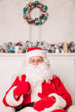 Old Father Christmas is resting and gesturing. Gorgeous Santa Claus is sitting in his chair and relaxing. He is giving thumb up with happiness. The man is Stock Image