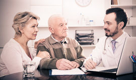 Old father with daughter visit doctor. Pensioner with mature daughter visit doctor at hospital to check health insurance Stock Photography