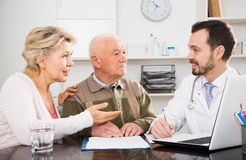 Old father with daughter visit doctor. Pensioner with mature daughter visit doctor at hospital to check health insurance Royalty Free Stock Image