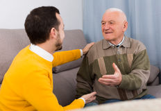 Old father and son friendly conversation. Elderly father and his son is warm and friendly conversation at home stock photo
