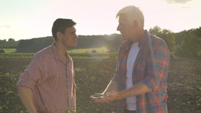Old father and son talking, dad holding soil on palm and talking, standing on ground in field, sunset and beautiful stock footage